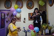 """Jennifer """"Dos Caras"""" ayuda en la decoración del consultorio de una amiga para la chaya (ritual andino que se basa en el acto de regar la tierra u otro bien con alcohol y elementos simbólicos) durante el carnaval de la ciudad de La Paz, Bolivia, el 17 de Febrero de 2012."""