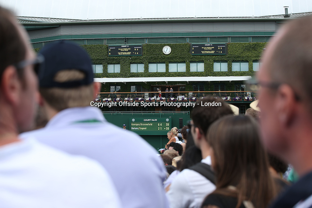 25 June 2014 Wimbledon Tennis - spectators watch the action on the outer courts.