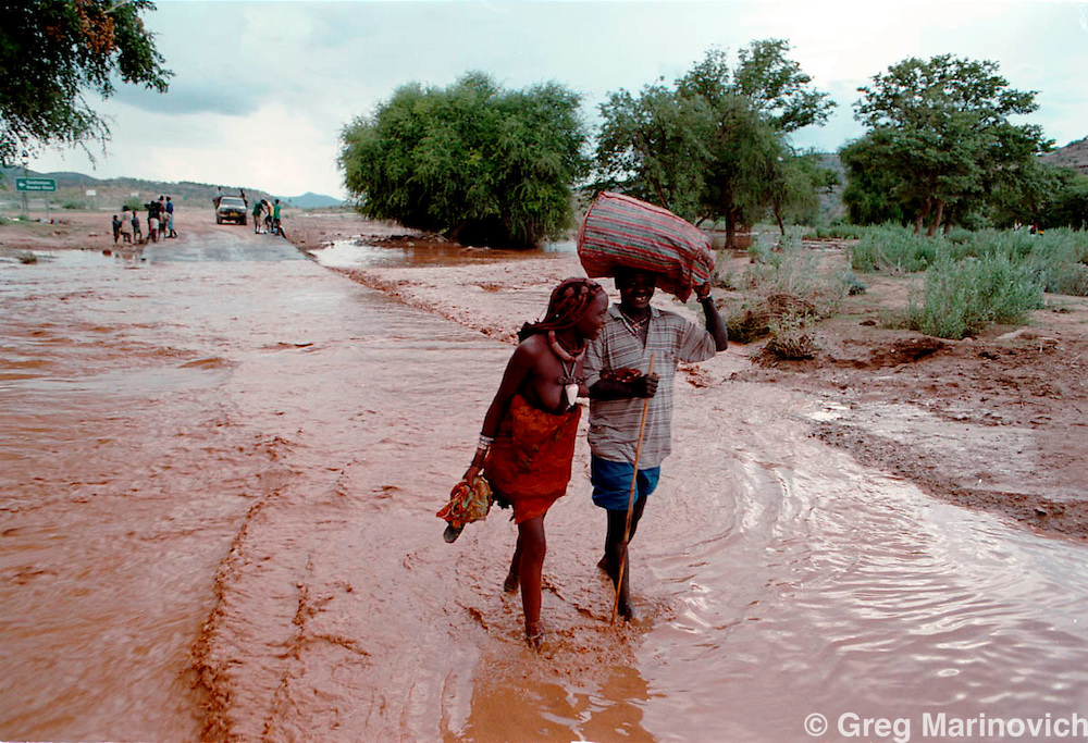 IPMG0725 Namibia, Opuwa, 2002:  Himba people cross a flooded bridge into Opuwa town, Koakoveld, Northern Namibia, March 4, 2002. The Himba people are staunch tradionalists and many live a semi-nomadic iron-age existence have a deep religious belief based on ancestral spirits.  .Photograph by Greg Marinovich / South Photographs