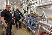 Vaktmestrene Joar Leon Berg (t.v.) og Hans Nossum i et av de mange tekniske rommene som finnes ved Mære Landbruksskole. De regner med at det kanskje blir mindre å gjøre når det store energieffektiviseringsanlegget settes i drift, men alle anlegg må uansett sjekkes jevnlig.