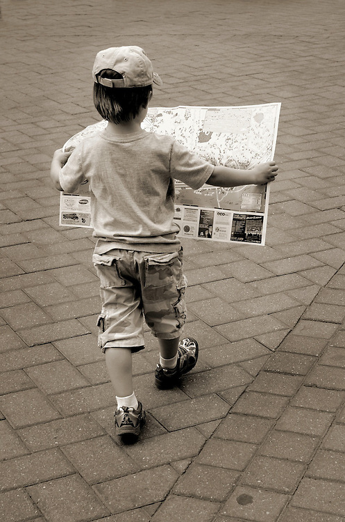 Young boy walking with map through Vail, Village, CO
