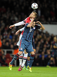 Arsenal's Per Mertesacker battles for the high ball with Bayern Munich's Javi Martinez - Photo mandatory by-line: Joe Meredith/JMP - Tel: Mobile: 07966 386802 19/02/2014 - SPORT - FOOTBALL - London - Emirates Stadium - Arsenal v Bayern Munich - Champions League - Last 16 - First Leg