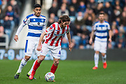 Joe Allen (Stoke) with the ball in front of Massimo Luongo (Queens Park Rangers) during the EFL Sky Bet Championship match between Queens Park Rangers and Stoke City at the Loftus Road Stadium, London, England on 9 March 2019.
