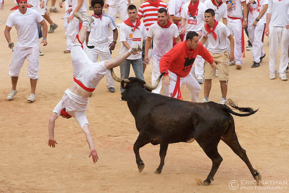A man is tossed around by a cow during the festivities following the encierro (bull run) during the annual festival of San Fermin (aka the running of the bulls) in Pamplona, Spain.