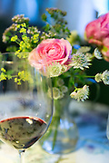 Glass of red wine and vase of flowers at Sonderho Kro Hotel and Restaurant quaint style on Fano Island, Denmark