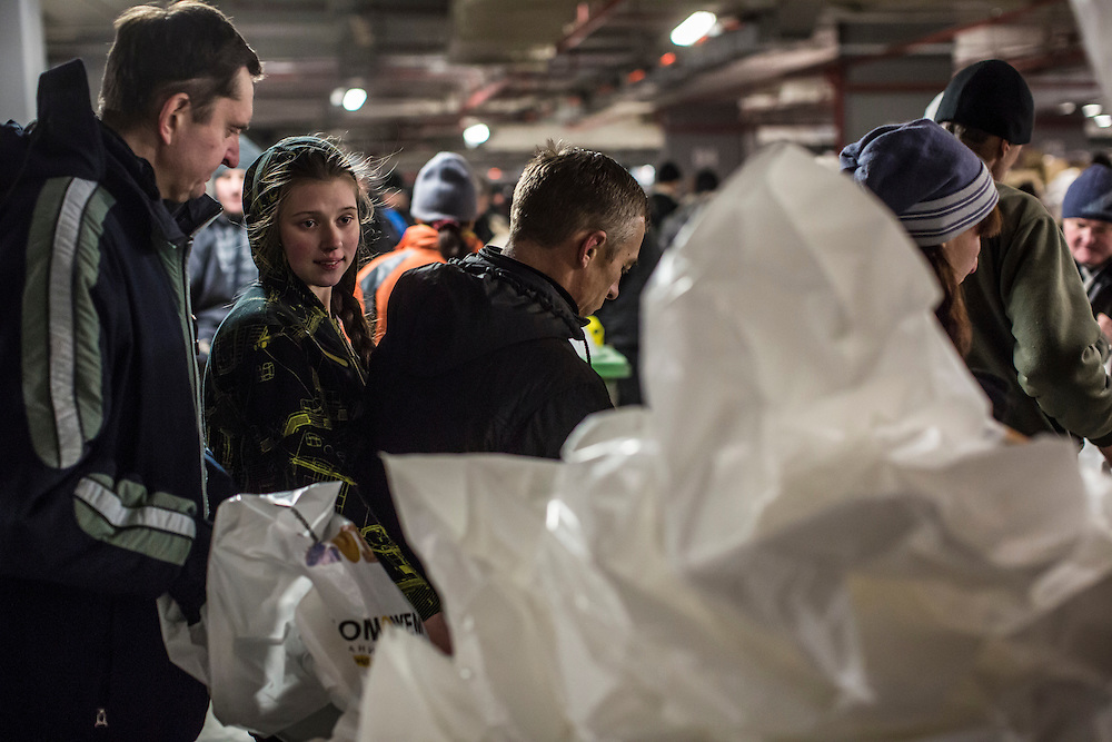 DONETSK, UKRAINE - JANUARY 26, 2015: Residents stand in line to receive bags of food and other supplies distributed to people in need at the Donbass Arena soccer stadium in Donetsk, Ukraine. With many residents finding it difficult to access bank accounts or find work, humanitarian needs are rising. CREDIT: Brendan Hoffman for The New York Times