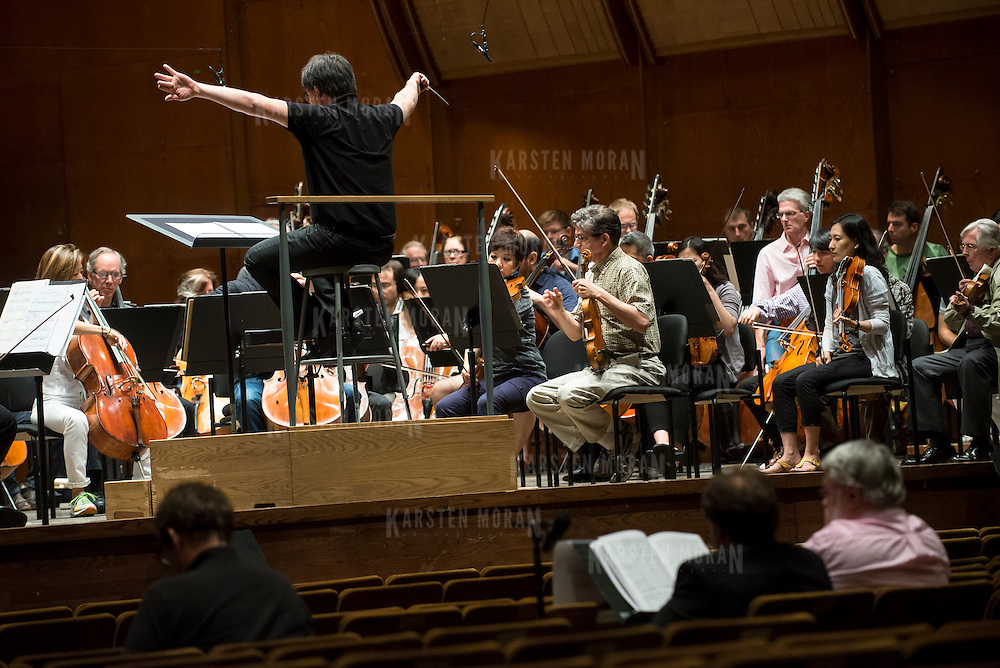 June 3, 2014 - New York, NY : As part of the New York Philharmonic Biennial, the orchestra solicited pieces from little-known composers and will choose three to play. Pictured here, Philharmonic Music Director Alan Gilbert, on podium, leads the New York Philharmonic as it performs a composition by Jesse Jones, who is visible at foreground center, working with mentor composer Christopher Rouse, far right, on Tuesday. CREDIT: Karsten Moran for The New York Times