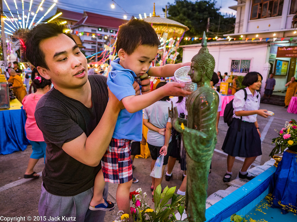25 NOVEMBER 2015 - BANGKOK, THAILAND: A Thai man and his son bathe a Buddha statue during Loy Krathong at Wat Yannawa in Bangkok. Loy Krathong takes place on the evening of the full moon of the 12th month in the traditional Thai lunar calendar. In the western calendar this usually falls in November. Loy means 'to float', while krathong refers to the usually lotus-shaped container which floats on the water. Traditional krathongs are made of the layers of the trunk of a banana tree or a spider lily plant. Now, many people use krathongs of baked bread which disintegrate in the water and feed the fish. A krathong is decorated with elaborately folded banana leaves, incense sticks, and a candle. A small coin is sometimes included as an offering to the river spirits. On the night of the full moon, Thais launch their krathong on a river, canal or a pond, making a wish as they do so.     PHOTO BY JACK KURTZ