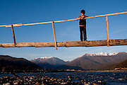 Bekan Khancoshvili (8) stands on a newly built bridge over the Alazani River, with Greater Caucasus Mountain Range in the backdrop.