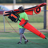 Scott Wilson appears to be a one man chain gang as brings them to the sidelines before the Falkner game against Okolona Friday night.