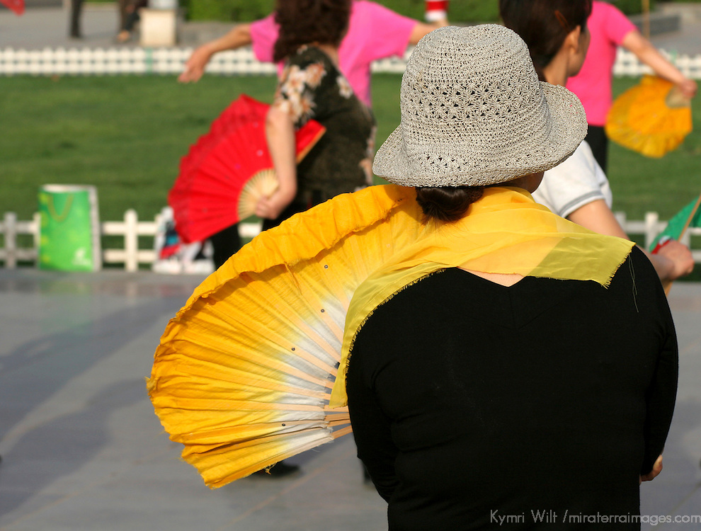 Asia, China, Shaanxi, Xian. A woman takes a break from tai Chi with her fan in Renman Square, Xian, China.