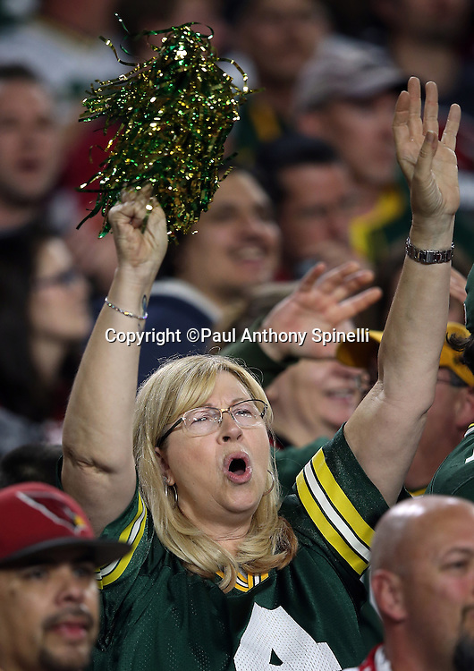 A Green Bay Packers fan cheers and waves a pom pom during the Green Bay Packers NFL NFC Divisional round playoff football game against the Arizona Cardinals on Saturday, Jan. 16, 2016 in Glendale, Ariz. The Cardinals won the game in overtime 26-20. (©Paul Anthony Spinelli)