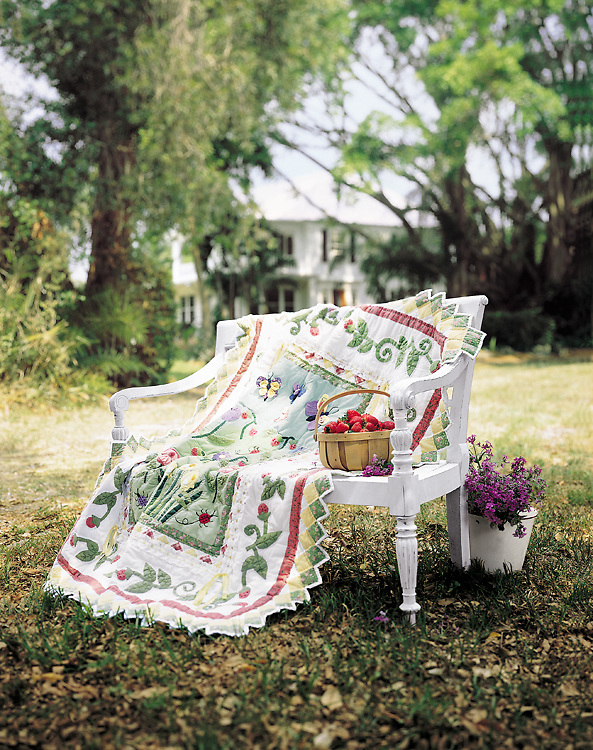 Piture of a quilt, effortlessy drapped over a wooden bench on a beautiful garden location.