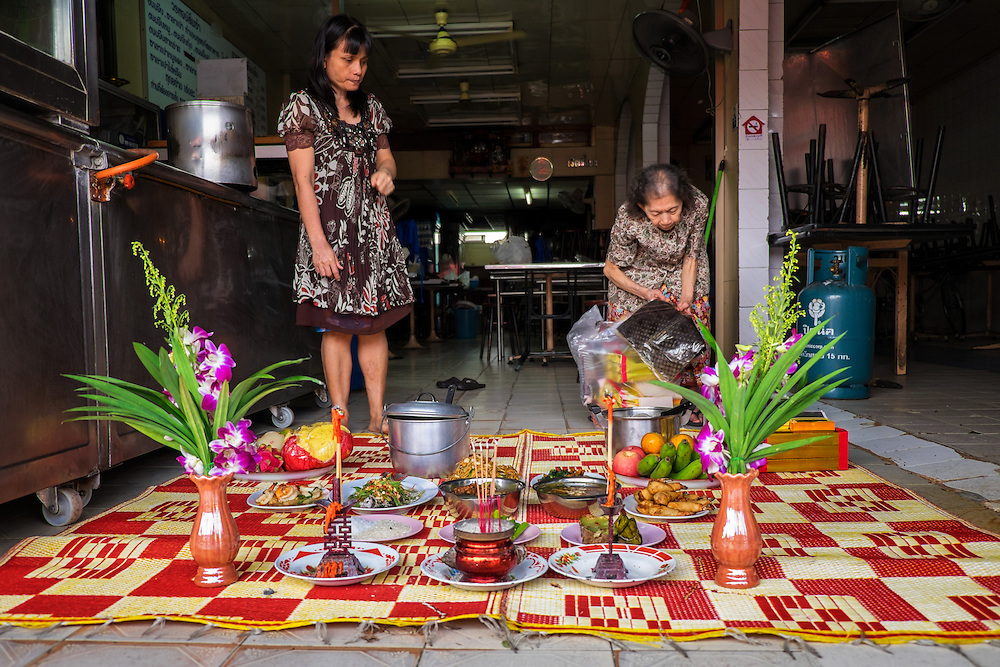 Resturant owners decorate their entrance way with gifts for their ancestors in Bangkok, Thailand