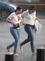 © Licensed to London News Pictures. 27/07/2018. London, UK. Two women get caught in a sudden downpour near Parliament as heavy rain ends the long dry spell. Photo credit: Peter Macdiarmid/LNP