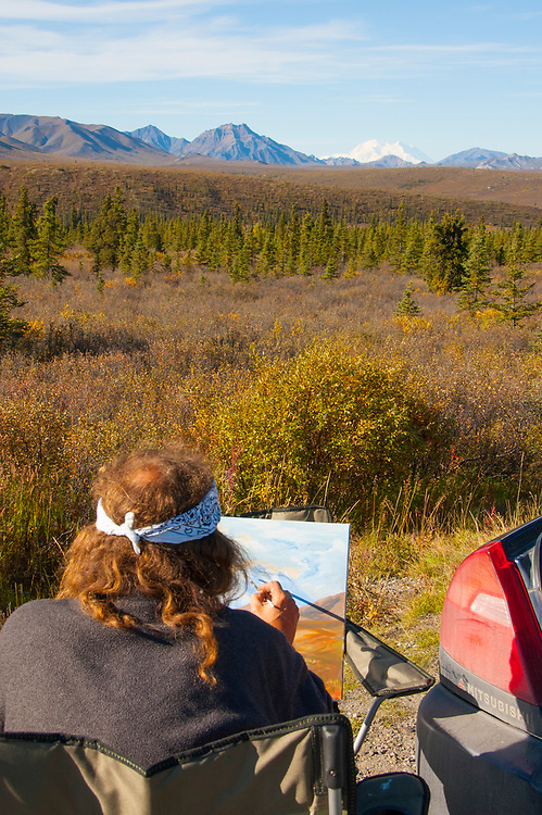 A roadside painter is capturing a rendition of Denali in the Alaska Range of Mts. with fall colors.