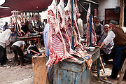 Kashgar: Uighur men talk at a local butchers at the weekly sunday animal market on the outskirts of Kashgar...Despite the migration of millions of Han Chinese to the western part of the Xinjiang Uighur Autonomous Region, the Uighur community continue to practice their muslim culture and resist the suppression of their cultural and religious traditions by the Chinese government....The chinese government has been criticised for the redevelopment of the old city, which has involved the destruction of many of the old houses in the town that were built without regulation, officials claiming them to be overcrowded and uncompliant with earthquake codes...Many in the chinese government believe Kashgar to a breeding ground for Uighur separatists, who Beijing claim to have links to terrorism...The european parliament has called for a halt to the cultural destruction of Kashgar, suggesting that Kashgar be added tot he UNESCO World heritage 'Silk Road' project, and calling on the chinese government to develop a genuine Han-Uighur dialogue to adopt more inclusive and comprehensive economic policies in Xinjiang in order to protect the cultural identity of the Uighur population..©JTanner/July 2011