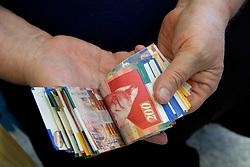 Middle East, Israel, Jerusalem, Israeli shekels (bills) in hands of moneychanger