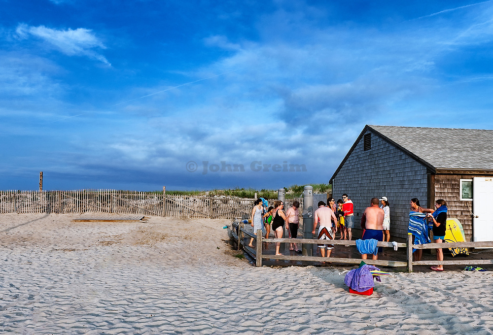 Vacationers wash off sand in outdoor beach showers, Nauset Beach, Cape Cod, Massachusetts, USA.