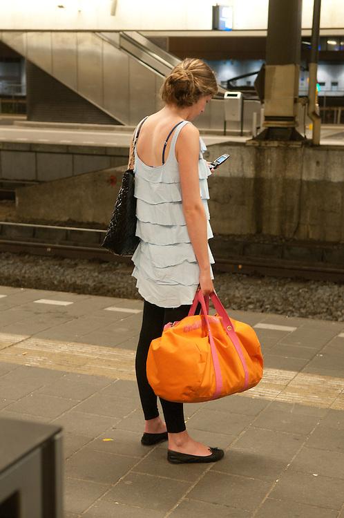 Nederland, Utrecht, 20100605..Jonge vrouw op het perron van station Utrecht. Met knaloranje tas, kijkt op haar mobiel    .Gerlo Beernink/Hollandse Hoogte