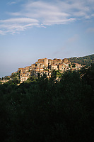 """PISCIOTTA, ITALY - 22 APRIL 2018: A view of the historical center of Pisciotta, Italy, on April 22nd 2018.<br /> <br /> Former restaurant owners Donatella Marino and her husband Vittorio Rimbaldo have spent the recent years preparing and selling salted anchovies, called alici di menaica, to a growing market thanks to a boost in visibility from the non-profit Slow Food.  The ancient Menaica technique is named after the nets they use brought by the Greeks wherever they settled in the Mediterranean. Their process epitomizes the concept of slow food, and involves a nightly excursion with the special, loose nets that are built to catch only the larger swimmers. The fresh, red anchovies are immediately cleaned and brined seaside, then placed in terracotta pots in between layers of salt, to rest for three months before they're aged to perfection.While modern law requires them to use PVC containers for preserving, the government recently granted them permission to use up to 10 chestnut wood barrels for salting in the traditional manner. The barrels are """"washed"""" in the sea for 2-3 days before they're packed with anchovies and sea salt and set aside to cure for 90 days. The alici are then sold in round terracotta containers, evoking the traditional vessels that families once used to preserve their personal supply.<br /> <br /> Unlike conventional nets with holes of about one centimeter, the menaica, with holes of about one and half centimeters, lets smaller anchovies easily swim through. The point may be to concentrate on bigger specimens, but the net also prevents overfishing."""