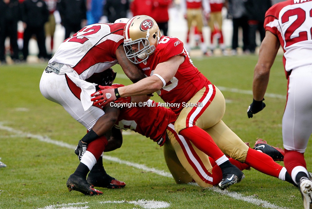 Arizona Cardinals kick returner Andre Roberts (12) gets gang tackled by San Francisco 49ers tight end Colin Cloherty (83) and a teammate on a kick return during the NFL week 17 football game against the San Francisco 49ers on Sunday, January 2, 2011 in San Francisco, California. The 49ers won the game 38-7. (©Paul Anthony Spinelli)