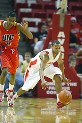 11 December 2010: Anthony Cousin scoops up a loose ball followed by Brad Birton during an NCAA basketball game between the Illinois - Chicago Flames (UIC) and the Illinois State Redbirds (ISU) at Redbird Arena in Normal Illinois.