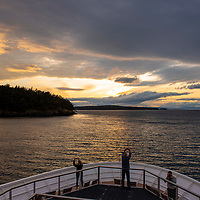Guests photograph the sunset from the bow of the National Geographic Venture in the San Juan Islands of Washington State near Jones Island Marine State Park.