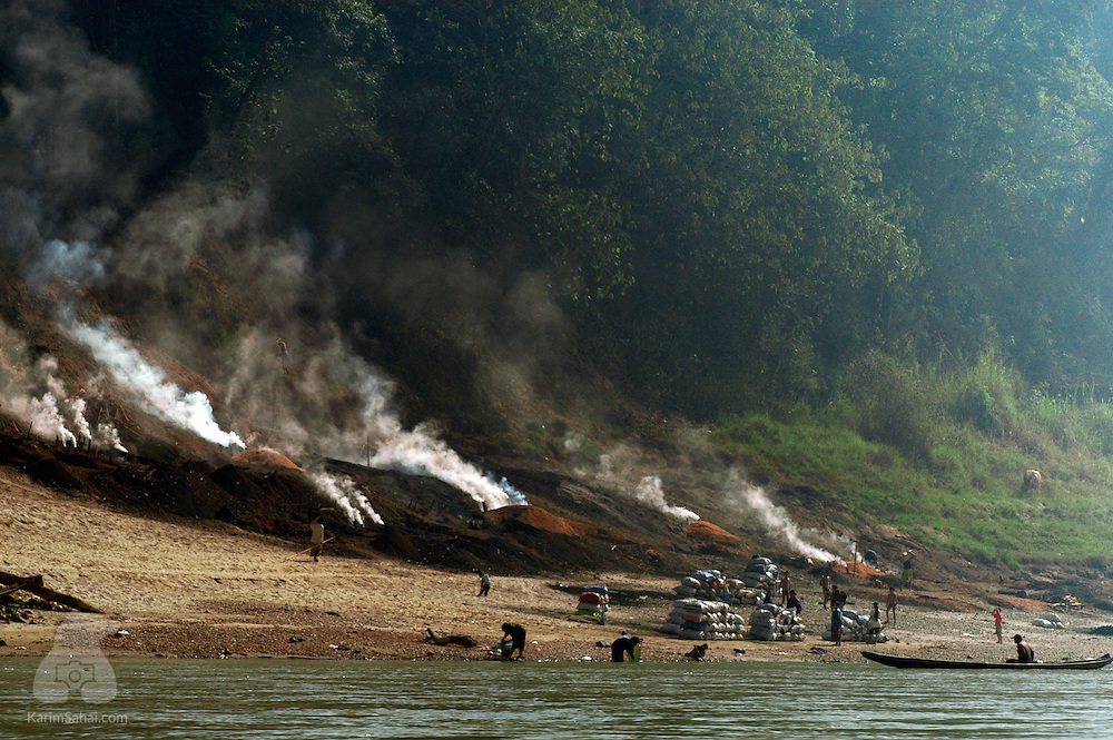 Smoke rising from coal furnaces on the edge of the Mekong river, Bokeo province, Laos
