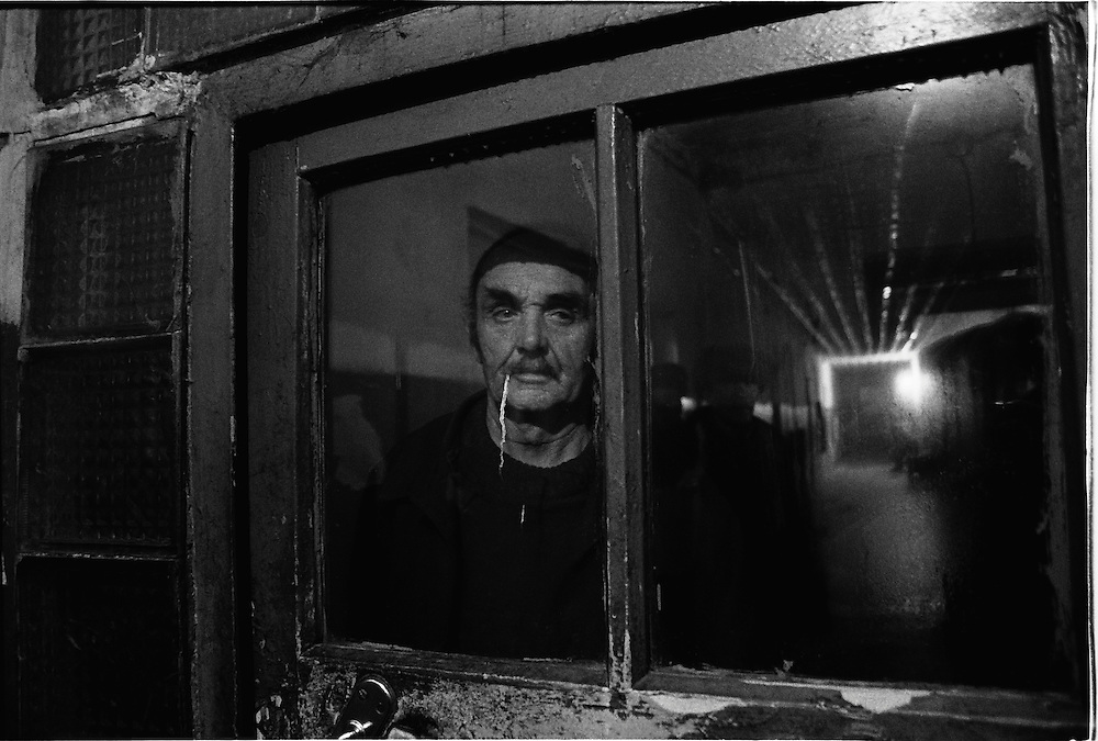 An old man stands behind a door's glass in barrack where he lives in house for  released an old prisoners in village Blagoveshenka, Kemerovo region, Eastern Siberia, Russia, 15 August 1995. Blagoveshensky house for an old former prisoners a special institution which is a part of a penitentiary system where live former prisoners which after released have age more then 55 years and haven't house or an apartment and relatives.