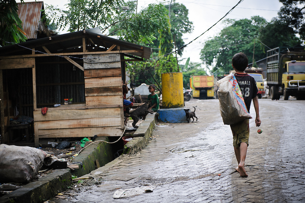 Ashuar, 12, returning home to the small village at the edge of the 'Trash mountain', Makassar, Sulawesi, Indonesia.