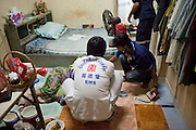 """Oct. 1, 2009 -- BANGKOK, THAILAND: Medics and volunteers from Poh Teck Tung help a woman who attempted suicide after an argument with her husband. Neighbors said the woman swallowed mosquito poison. She was unconscious and unresponsive and the crew rushed her to a nearby hospital. They left before getting final word on her status.  The 1,000 plus volunteers of the Poh Teck Tung Foundation are really Bangkok's first responders. Famous because they pick up the dead bodies after murders, traffic accidents, suicides and other unplanned, often violent deaths, they really do much more. Their medics respond to medical emergencies, from minor bumps and scrapes to major trauma. Their technicians respond to building collapses and traffic accidents with heavy equipment and the """"Jaws of Life"""" and their divers respond to accidents in the rivers and khlongs of Bangkok. The organization was founded by Chinese immigrants in Bangkok in 1909. Their efforts include a hospital, college tuition for the poor and tsunami relief.    Photo by Jack Kurtz / ZUMA Press"""