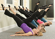 Colleen Ketchum, front, leads a class doing the bridge position with kick at Beyond Barre studio in Warwick on Thursday, Jan. 6, 2010.
