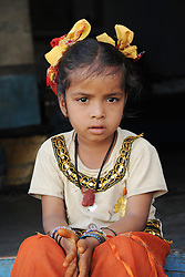 Charming child sitting on stoop outside of her family home. Photo taken while traveling in Jodhpur, India, with Steve McCurry.