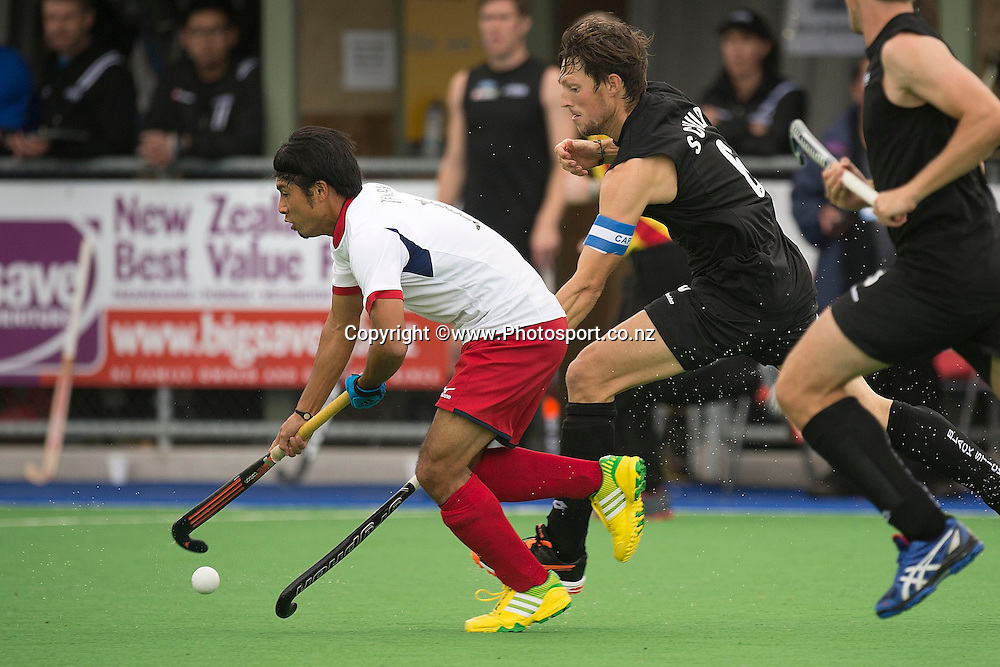 Kenta Tanaka (L) of Japan dribbles the ball with Simon Child captain of New Zealand in defense during the Black Sticks Men v Japan international hockey match at the Coastlands Kapiti Sports Turf in Paraparaumu on Friday the 22nd of November 2014. Photo by Marty Melville/www.Photosport.co.nz