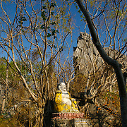 A laughing Buddha statue nestled on top of a mountain pass at Wat Khao Tham Talu in Ratchaburi province, Thailand