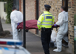 © Licensed to London News Pictures. 21/09/2017. London, UK. A body is removed on a stretcher from a house where police and the fire brigade attended and found a burnt body in the garden in Southfields, south London A 40-year-old man and a 34-year-old woman were arrested at the scene on Wednesday, 20 September on suspicion of murder. Photo credit: Peter Macdiarmid/LNP