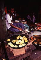 A man cooking traditional donuts in the Indian capital city of New Delhi.