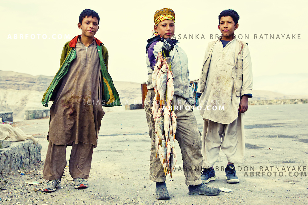 Young boys sell fresh fish along the Kabul - Jalalabad road, Afghanistan