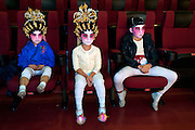 from the left: Wong Yuet (5), Yan-Ting (4), Siu-Kit (8) from Cha Duk Chang are waiting for further instructions during a very last rehearsal of the Opera they're about to perform. <br /> <br /> Cha Duk Chang (查篤撐) is a Children's Cantonese Opera Association from Hong Kong that aim is to use the traditional art of Chinese Opera as a method of education and to maintain interest in traditional culture among Hong Kong's children.<br /> <br /> At the very end of 2013, the children of Cha Duk Chang performed in Foshan, in the Guangdong province of China, a new original Opera written by Stella Ma, playwright and director of the association, called &quot;Rehearsing for a Great Fun Show&quot;. Unlike traditional Cantonese operas, this opera is designed for children. Its music and lyrics are easier to sing and to memorize.