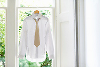 Dress shirt and tie on hanger in domestic window