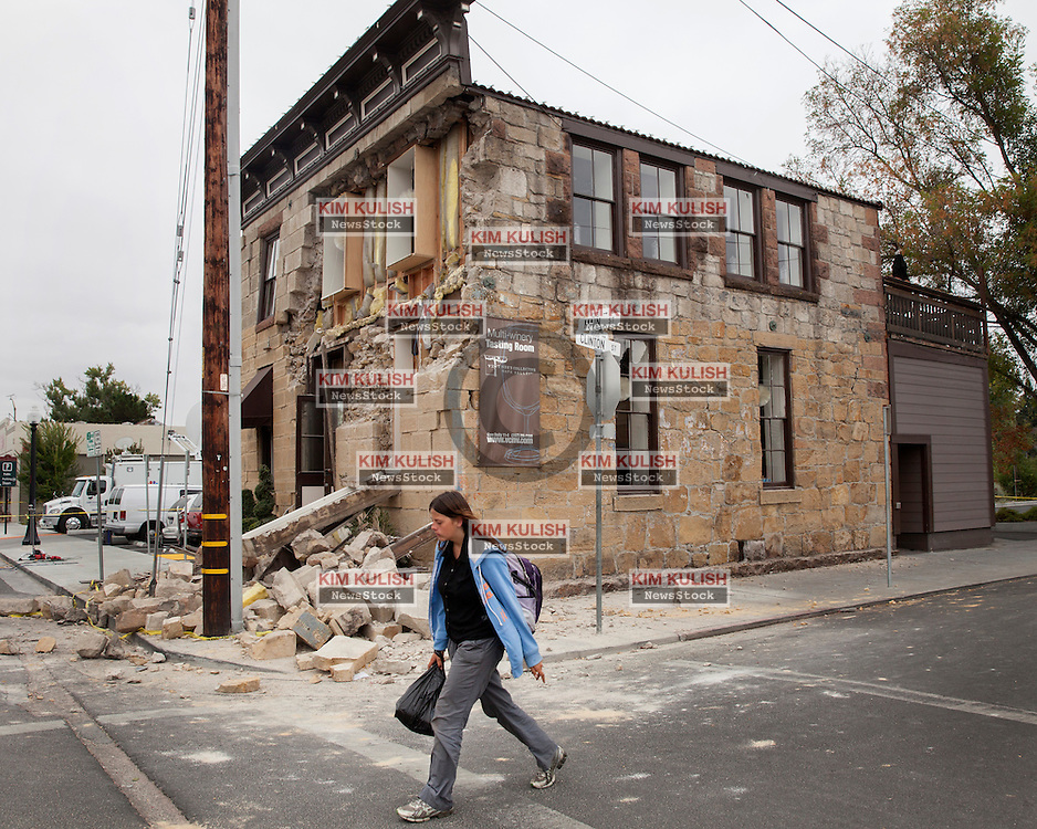 A woman walks past the Vintner's Collective wine tasting room that was damaged in downtown Napa following the  6.0 earthquake that struck in southern Napa County on August 24, 2014.
