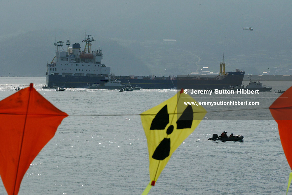 """SURROUNDED BY JAPANESE POLICE AND COAST GUARD GREENPEACE INFLATABLES """"PROTEST"""" ( bear witness...), WITH KITES FROM THE ARCTIC SUNRISE GREENPEACE SHIP, IN UCHIURA BAY, BESIDE THE TAKAHAMA NUCEAR PLANT, AS BNFL SHIP 'PACIFIC PINTAIL' DEPARTS LATE AFTERNOON AFTER COLLECTING REJECTED PLUTONIUM MOX FUEL, FOR SHIPMENT BACK TO THE UNITED KINGDOM. TAKAHAMA, JAPAN. 04/07/02. .PIC © JEREMY SUTTON-HIBBERT/GREENPEACE 2002..*****ALL RIGHTS RESERVED. RIGHTS FOR ONWARD TRANSMISSION OF ANY IMAGE OR FILE IS NOT GRANTED OR IMPLIED. CHANGING COPYRIGHT INFORMATION IS ILLEGAL AS SPECIFIED IN THE COPYRIGHT, DESIGN AND PATENTS ACT 1988. THE ARTIST HAS ASSERTED HIS MORAL RIGHTS. *******"""