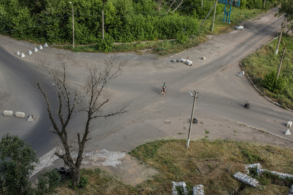 AVDIIVKA, UKRAINE - JULY 9, 2016: Pedestrians pass through an intersection dotted with tank traps and trenches near the front lines in Avdiivka, Ukraine. The town is now one of the most active areas of fighting along the line of control between the Ukrainian government and Russian-backed rebels. CREDIT: Brendan Hoffman for The New York Times