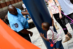 A security officer and a boy play as thousands of pedestrians, cyclist, skaters, joggers participate in the third annual Philly Free Streets event at a 4mi (6.4km) car-free section of North Broad Street, in Philadelphia, PA, on August 11, 2018.