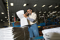 Man using telephone in factory reading newspaper
