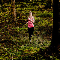 Model released - Kvinde sidder på træstamme og holder pause efter træning i skoven Løbetræning i skoven - trailløb