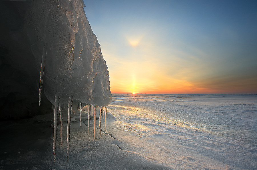 Sunrise illuminates icicles on ice cave in winter on Lake Ontario