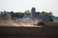 Stirring up a cloud of dust, a red Case IH tractor rakes through a field on the plains of Illinois.