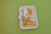 A detail of half-eaten chips (fries) left in a styrofoam dish, on a green cafe table in central London.